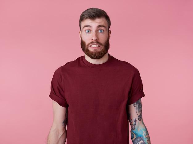 Что-то не так! молодой привлекательный татуированный рыжий бородатый мужчина в пустой футболке, выглядит шокированным и грустным, стоит на розовом фоне. Бесплатные Фотографии