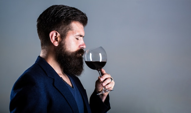 Sommelier, degustator with glass of red wine, winery, male winemaker. Premium Photo