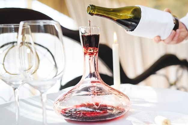 A sommelier pouring red wine into decanter Premium Photo