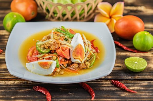 ソムタム。木製のテーブルに塩味の卵とタイのスパイシーグリーンパパイヤサラダ(somtum khai kem) Premium写真