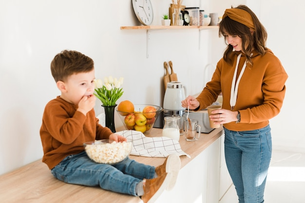Son assisting mom in kitchen Free Photo