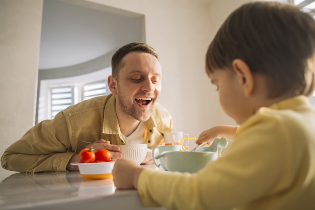 Son and father eating in the kitchen Free Photo