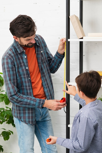 Son and father measuring a self Free Photo