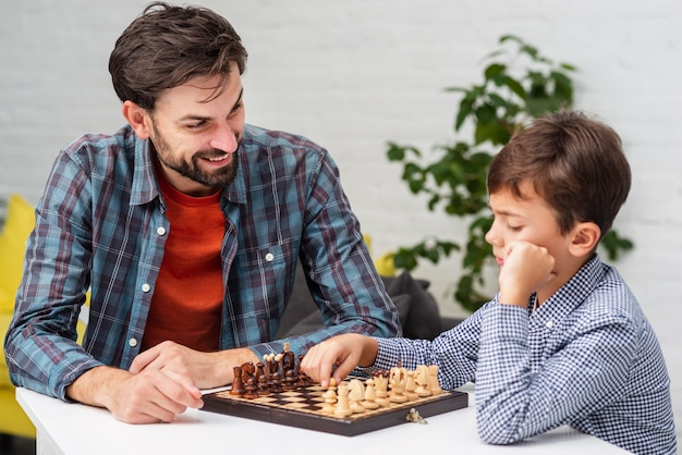 Son and father playing chess Free Photo