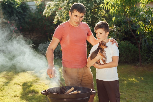 Son and father preparing food together at picnic Free Photo