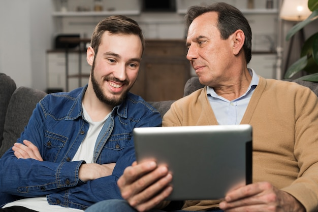 Son and father smiling at tablet in living room Free Photo
