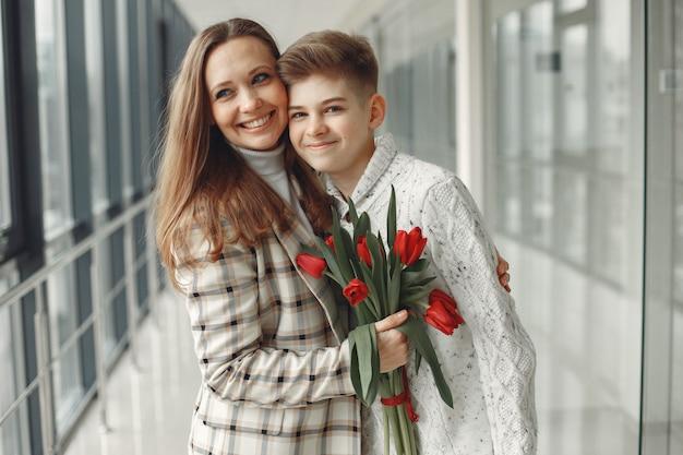 Сын дарит маме букет красных тюльпанов в современном зале Бесплатные Фотографии