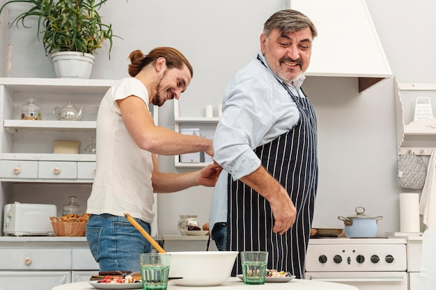 Son helping father with kitchen apron Free Photo