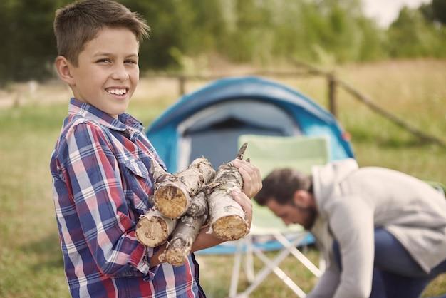 일 모닥불을 점화하기 위하여 그의 아버지를 돕는 아들 무료 사진