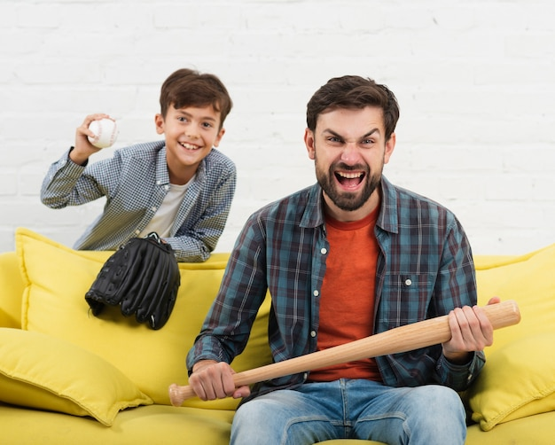 Son holding a ball and father a a baseball bat Free Photo
