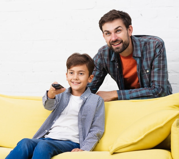 Son holding remote control and watching tv with his father Free Photo