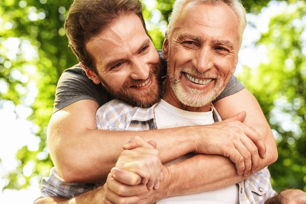 Son hugs old man. family walking in park together. Premium Photo