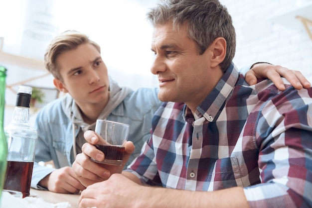 Son is trying to stop drinking father. Premium Photo