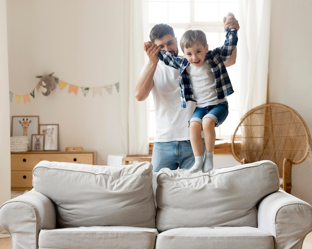 Son jumping on the sofa and being held by father Free Photo