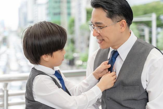 息子はビジネス地区の都市で彼の父のためにスーツの襟を作りました 無料写真