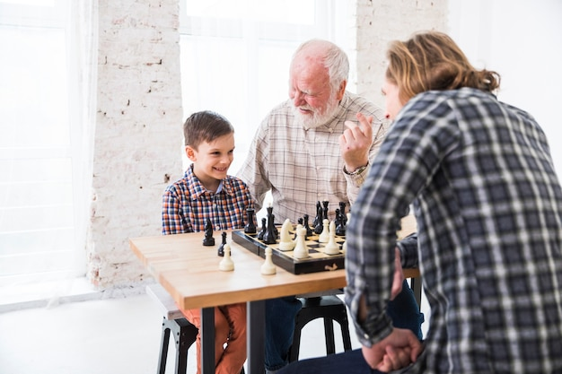 Son playing chess with dad Free Photo