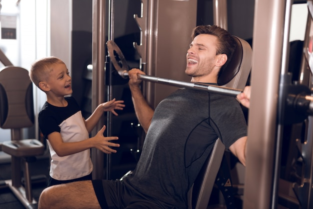 Son support to father while lifting the barbell Premium Photo