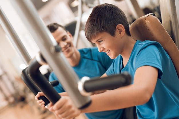 Son trains pectoral muscles while dad is watching. Premium Photo
