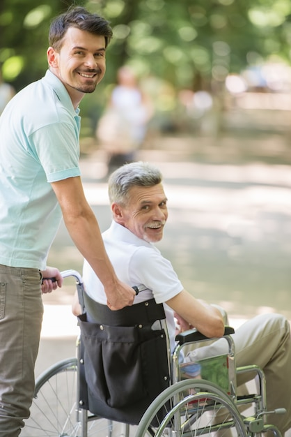 Son walking with disabled father in wheelchair at park Premium Photo