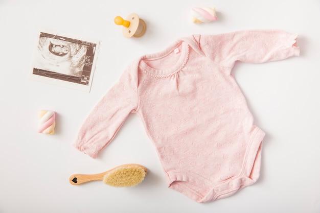Sonographyの画像とピンクのbaby onesie;おしゃぶり;マシュマロ;白い背景にブラシ 無料写真