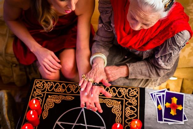 Soothsayer during a session doing palmistry Premium Photo