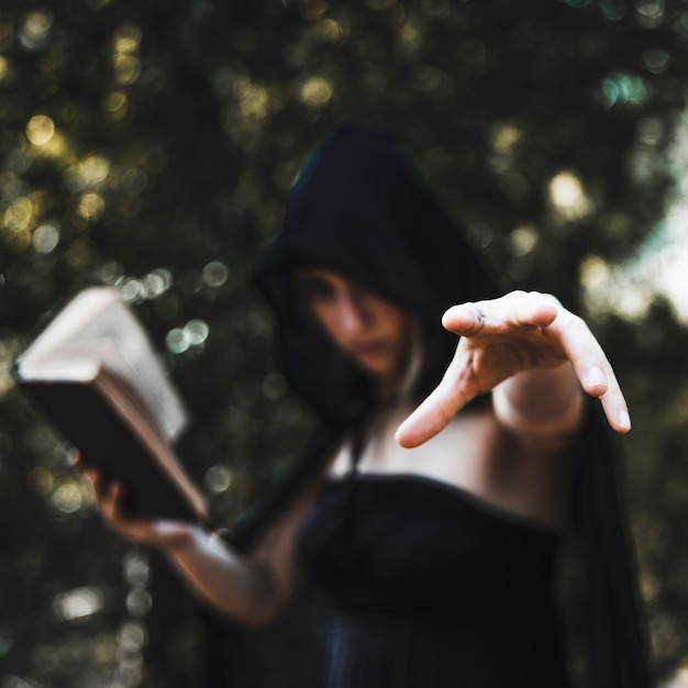 Sorceress casting spell in woods daytime Free Photo