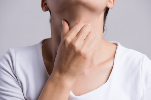 Sore throat. woman hand touching her ill neck. healthcare and medical concept. Premium Photo