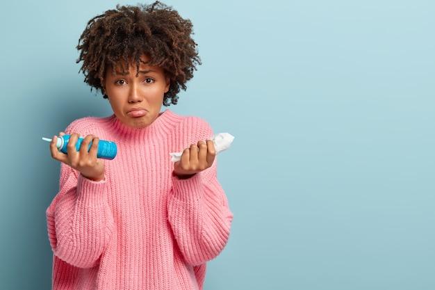 悲しい女性は季節性アレルギーに苦しんでおり、ハンカチと鼻のエアロゾルを持っており、アフロの髪型をしており、特大のピンクのジャンパーを着ており、青い壁にモデルがあり、テキスト用の空白があります 無料写真