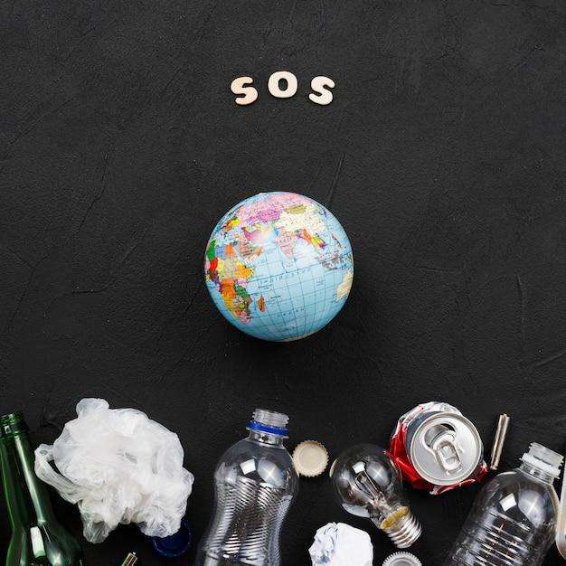 Sosの手紙、地球と暗い背景にゴミの山 Premium写真