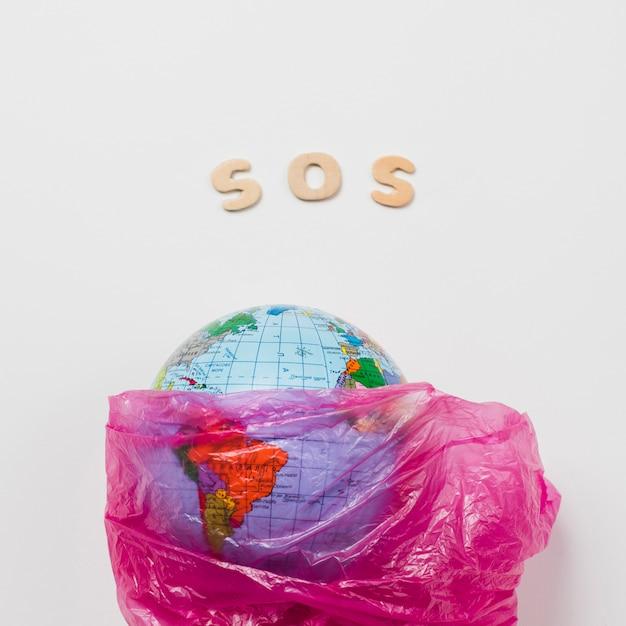 Sosと言ってレタリングの横にあるプラスチックの中の地球 無料写真