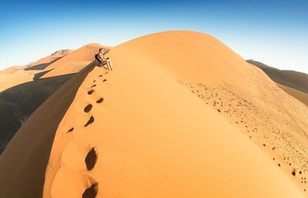 Sossusvleiナミビアの砂丘45で砂の上に座っている孤独な男性旅行者 Premium写真