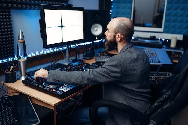 Звукорежиссер смотрит на монитор на пульте дистанционного управления в студии звукозаписи. Premium Фотографии