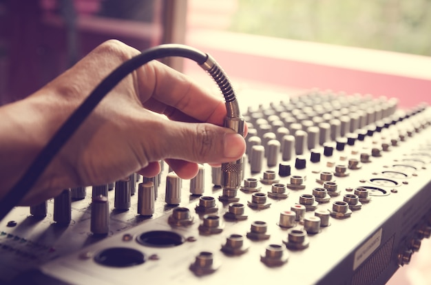 Sound engineer's hand,jack cable with volume control,this image adjust color to vintage to Premium Photo