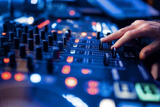 Звукооператор руки у пульта управления громкостью в студии звукозаписи. Premium Фотографии