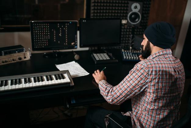 サウンドプロデューサーはスタジオでオーディオ機器を操作します。 Premium写真