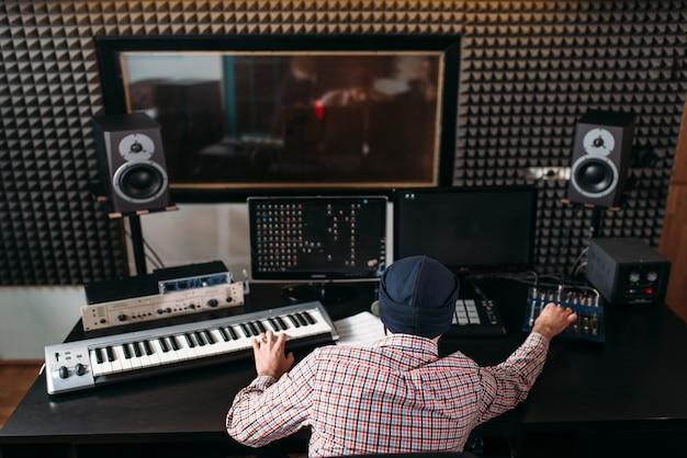 Звукорежиссер работает с аудиоаппаратурой в студии. Premium Фотографии