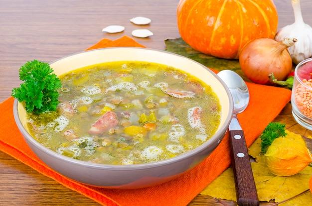 Soup from pumpkin, lentil and sausage Premium Photo