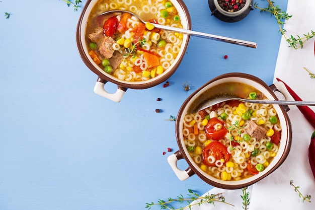 Soup with small pasta, vegetables and pieces of meat in  bowl on  blue table. italian food. top view. flat lay Free Photo