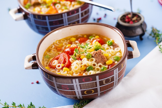 Soup with small pasta, vegetables and pieces of meat in  bowl on  blue table. italian food. Free Photo