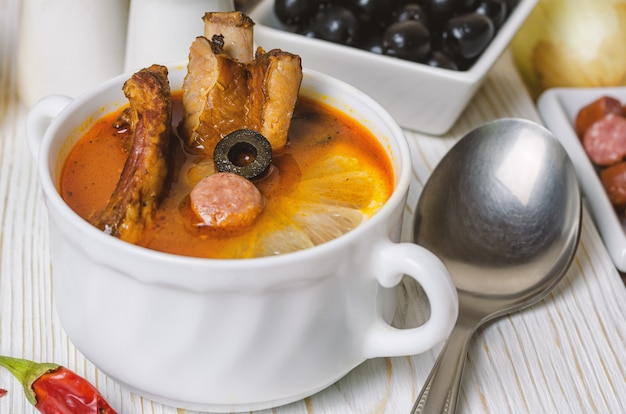Soup with smoked meat, olives and lemon. solyanka soup Premium Photo