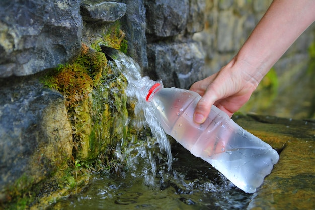 Source of spring water bottle filling holding hand Premium Photo
