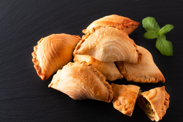 South east asia origin food concept homemade chicken curry puffs on black slate stone background with copy space Premium Photo