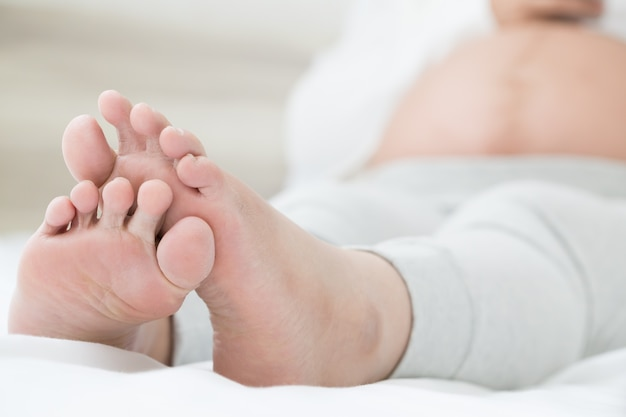 Southeast asian pregnant women with swelling feet, pain foot and lying on bed in the room. Premium Photo