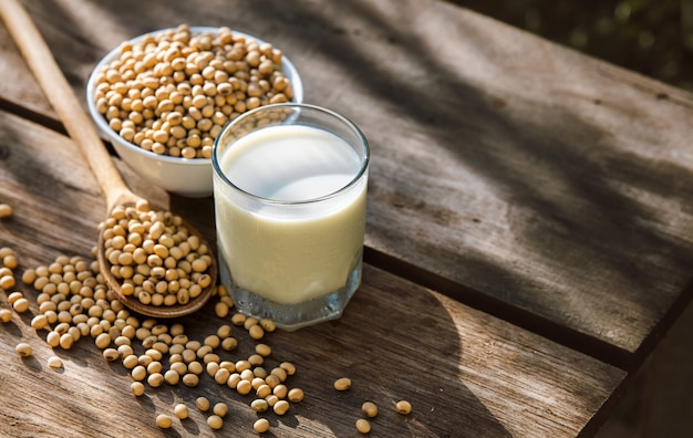 Soy milk cool and soybeans on wooden table Premium Photo