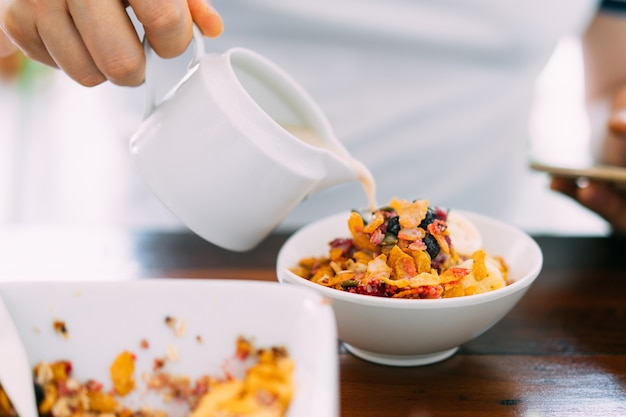 Soy milk pouring in acai bowl mix with fresh mango, avocado, banana, berries, sunflower seeds, chia seeds and cereal. superfood breakfast bowl for healthy and vegan people. Premium Photo