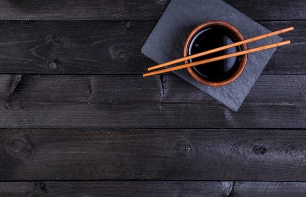 Soy sauce, chopsticks on black stone, top view Premium Photo
