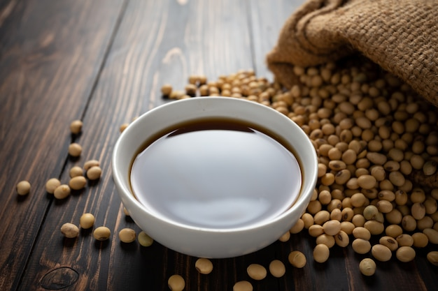 Soy sauce and soy bean on wooden table. Free Photo