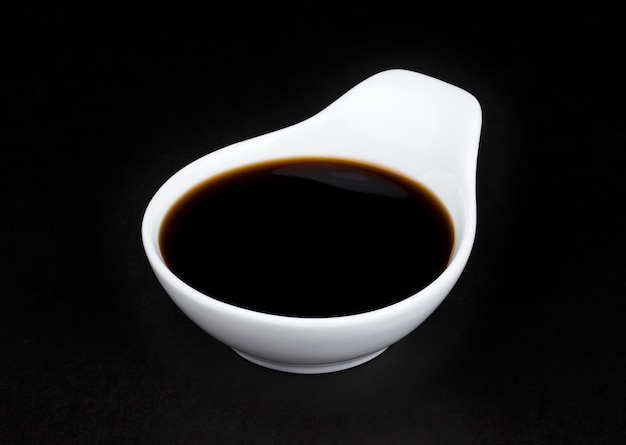 Soy sauce in white bowl on black background Premium Photo