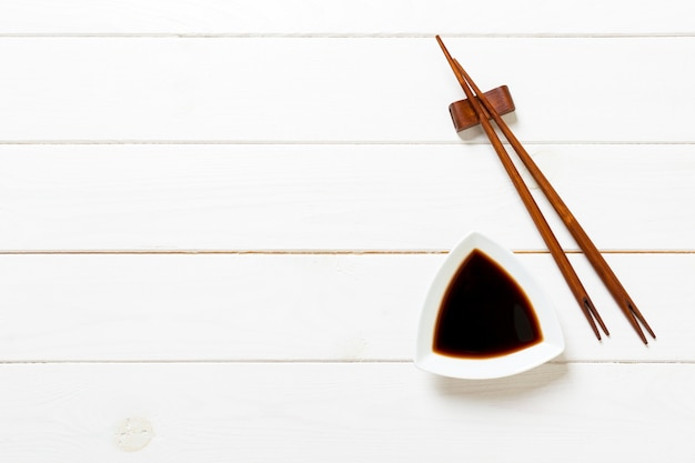 Soy sauce with chopsticks on white wooden table Premium Photo