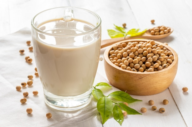 Soy or soya milk in a glass with soybeans in wooden bowl Premium Photo
